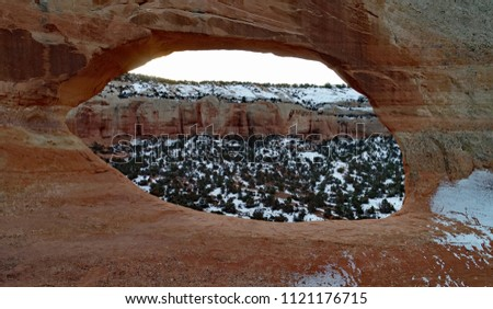 Wilson Arch, sandstone arch with snow in the background near Moab Utah #1121176715