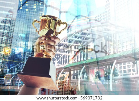 Win concept,Man holding up a gold trophy cup is winner in a competition with cityscape background.