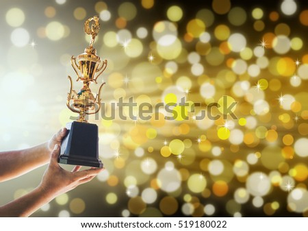 Win concept,Man holding up a gold trophy cup is winner in a competition with gold background. #519180022