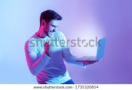 Win online. Man expresses emotions of happiness, looking in laptop with luminous screen, isolated in neon, studio shot