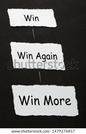 Win, Win Again and Win More text on 3 piece of torn paper over black surface. #1479276857