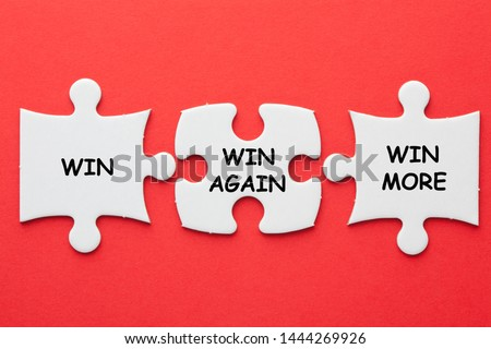 Win, Win Again and Win More text on 3 pieces paper puzzle on a red background. Business concept. #1444269926