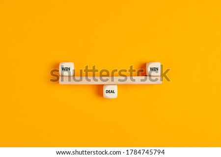 Win win situation in a business deal. Wooden blocks are designed as a seesaw on balance with win win text written on cubes.