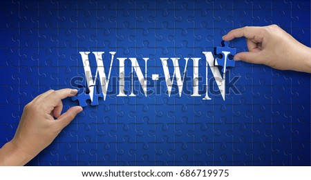 win win word on Jigsaw puzzle - business concept. Man hand holding a blue puzzle to complete the word win-win divided over them concept of the solution to a problem, challenge, plan and strategy. #686719975