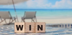 Win word on wooden cubes with ocean landscape. Business concept.