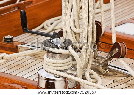 Winch with crank, pulleys and rope on a sailing boat