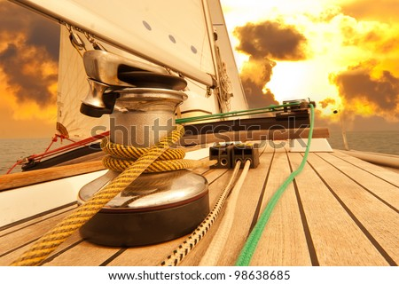 Winch with rope on sailing boat in the sea at sunset