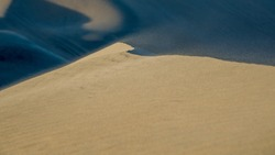 wind blowing beige sand grains over the ridge of a dune. blurred motion in the foreground and shadow in the background.