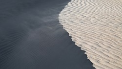 Wind blowing sand at the top of a sand dune. Abstract image, showing light and dark sides