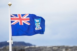 Wind blown tattered Falkland Islands flag with a cloudy sky. Some Motion Blur