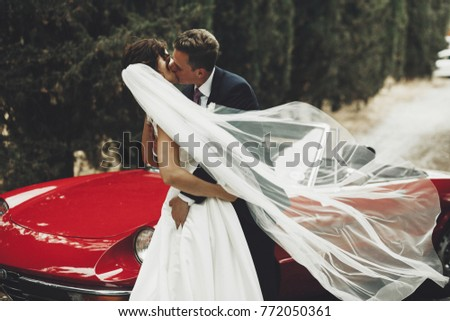 Wind blows bride's veil while groom hugs her standing before a red retro cabriolet