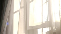 wind blows through the open window in the room. Waving white tulle near the window. Morning sun lighting the room, shadow background overlays.