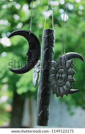 Wind chime with vintage suns, moons, stars and other celestial bodies with faces on a background of green leaves in a garden #1149122171