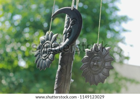Wind chime with vintage suns, moons, stars and other celestial bodies with faces on a background of green leaves in a garden #1149123029