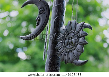 Wind chime with vintage suns, moons, stars and other celestial bodies with faces on a background of green leaves in a garden #1149123485