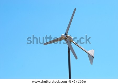Wind electric turbine generator at blue sky background