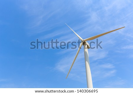 Wind energy turbine against white cloud and blue sky