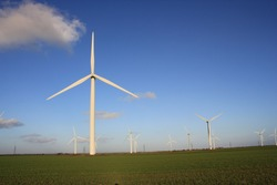 Wind farm turbines that produce electricity energy. Windmill Wind power technology productions Wind turbines standing in green field - stock photo