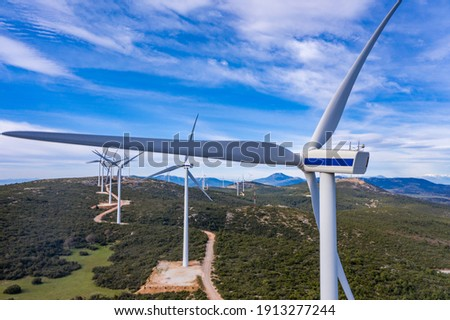 Wind farm, Wind turbines and curvy road on the hill, aerial drone view. Green ecological power energy generation. Alternative energy plant, blue cloudy sky,  Stock photo ©