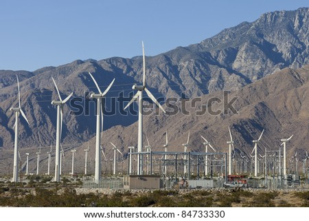 Wind farm with power station and mountains in the background
