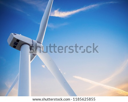 wind mill or also wind-turbine on wind farm in rotation on outdoor with sun and blue sky