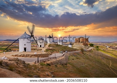 Wind mills and old castle in Consuegra, Toledo, Castilla La Mancha, Spain. Picturesque panorama landscape with road and view to ancient walls and windmills on blue sky with clouds. Foto stock ©