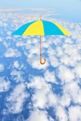 Wind of change concept.Umbrella in Ukrainian flag colors flies in sky over white clouds.Mary Poppins Umbrella.