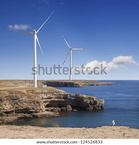 Wind power plants on a rock by the sea