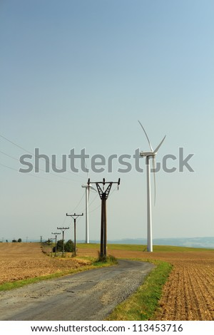 Wind power station and electricity pylons near the road