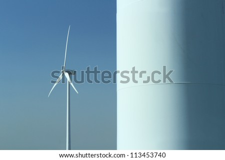 Wind power station and turbine as alternative energy source. A part of another pylon of wind turbine in the foreground on the right side.
