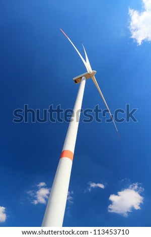 Wind power station wind turbine against clear blue sky and small clouds