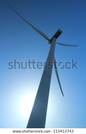 Wind power station - wind turbine as alternative energy source against clear blue sky with the sun as a source of backlight
