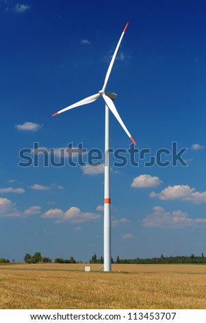 Wind power station with turbine against blue sky