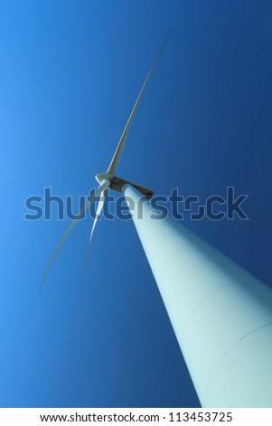Wind power station with wind turbine as alternative energy source against clear blue sky vertical orientation
