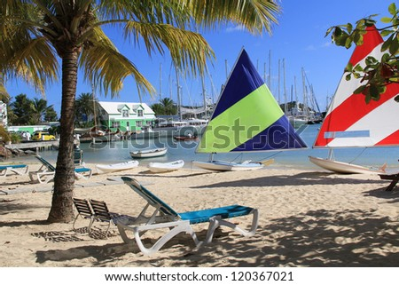 Wind surfing boards sitting on a hotel beach near Falmouth Harbour Marina in Antigua Barbuda.