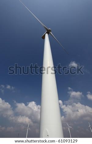 Wind turbine against a blue sky; wide-angle view