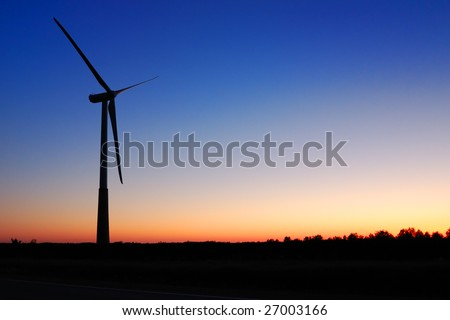 Wind turbine against an evening glow background