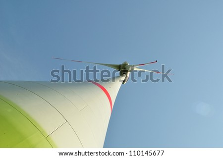Wind turbine against blue sky made from the bottom
