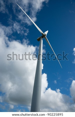 Wind turbine against clouds and blue sky. - stock photo