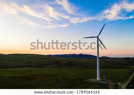Wind turbine, alternative energy, wind energy, one windmill in a field in the mountains, top view of a wind turbine at sunset. Stock photo ©