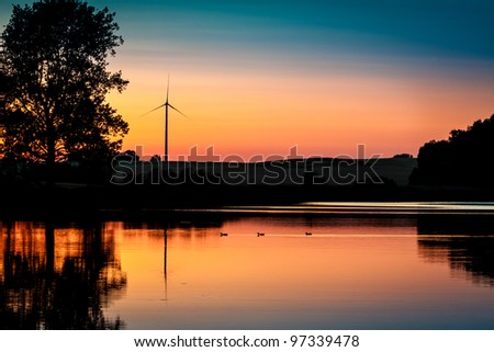 Wind Turbine and sunset at lake in summer