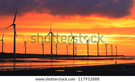 wind turbine array silhouettes at sea shore