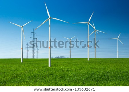 Wind turbine as renewable energy source, electricity pylon, wiring,  summer landscape with clear blue sky and green meadow