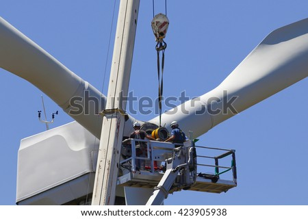 Wind turbine being repaired, assisted by crane and elevator