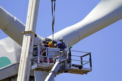 Wind turbine being repaired, manual workers maintenance