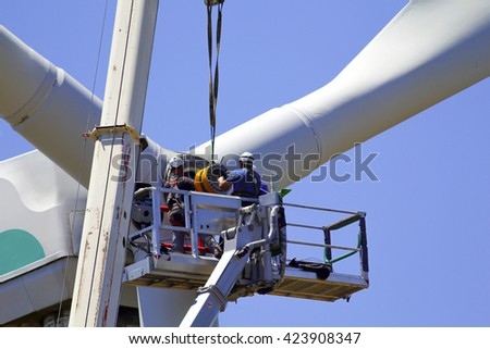 Wind turbine being repaired, manual workers maintenance