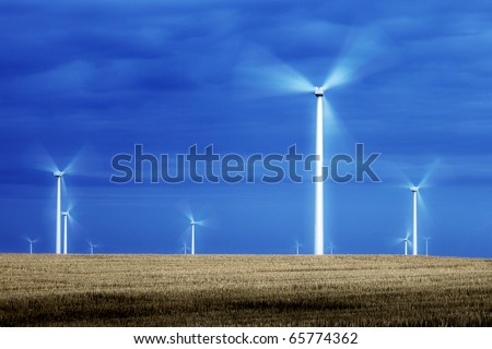 Wind turbine blade spinning like electric pinwheels in the middle of a wide open field.