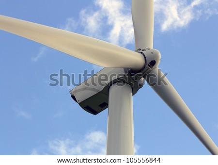 Wind turbine closeup on the blue sky
