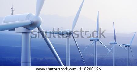 Wind turbine farm against distant mountains (3d graphic)
