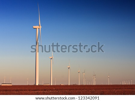 Wind Turbine farm located in a cotton field in West Texas.  The cotton has been harvested as is bailed for pick up.